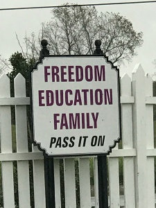 "White sign with red and black letters on a white fence, reading ""Freedom, Education, Family, Pass it on."""
