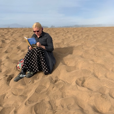 This is a photo of me sitting in the red sand and reading Narrating Violence, Constructing Collective Identities: 'To Witness These Wrongs Unspeakable' by Giti Chandra.