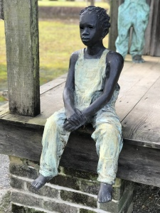Statue depicts a Black child in yellow clothes, seated, who was enslaved at the Whitney Plantation near New Orleans, LA.