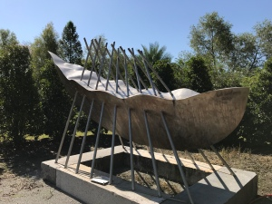 Picture of a long boat-shaped metal sculpture surrounded by trees.