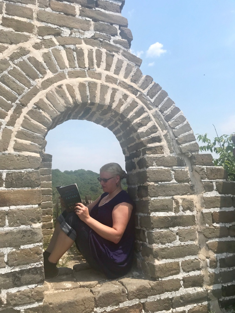 This is a photo of me sitting on the Great Wall of China, reading A People's Future of the United States.